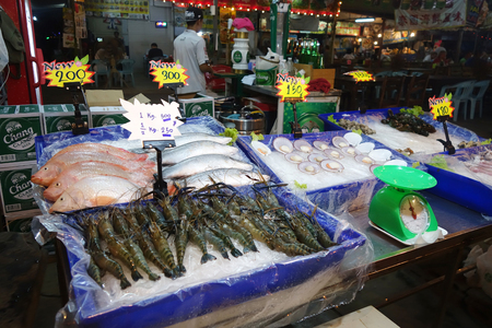 fish vendor: PATTAYA, THAILAND - 19 NOV, 2016: Street food stall in Pattaya. Street food is ready-to-eat food or drink sold by a hawker, or vendor, in a street or other public place, such as at a market or fair.