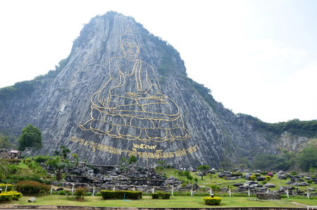 crave: Buddha carved on cliff mighty laser, the major attractions of Pattaya at Cheechan mountain, in Pattaya, Chonburi Thailand. Stock Photo