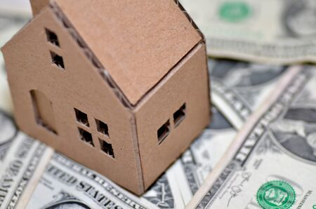 permanence: Paper made house stands on dollar money