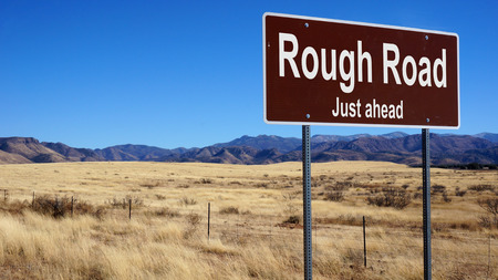 rough road: Rough Road road sign with blue sky and wilderness