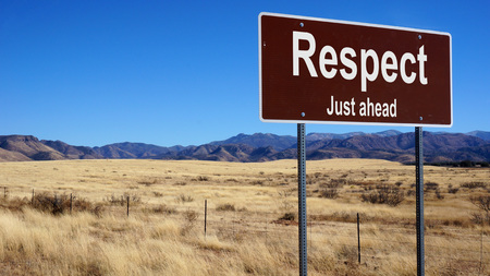 Respect brown road sign with blue sky and wilderness Stock Photo