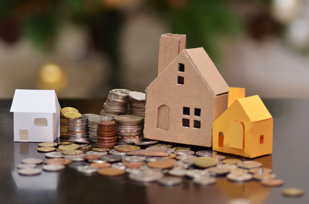 Paper house and stacks of coins standing. House loan concept Standard-Bild
