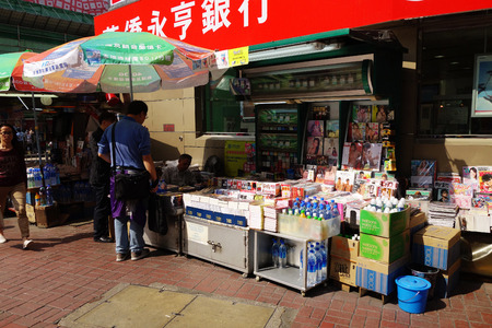 news stand: HONG KONG - NOVEMBER 26, 2016: News stand and vendor located in the busy district of Mongkok, Hong Kong