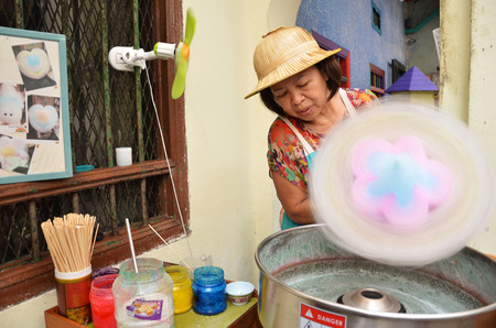 COSTUMERS: IPOH, MALAYSIA-27 DECEMBER, 2016: Unidentified vendor prepares candy cotton and the costumers choosing sweets. Cotton candy is one of the most sold sweets at the fairs. Editorial