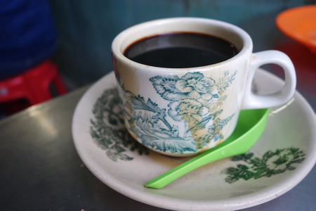 kopi: Steaming traditional oriental Chinese kopitiam style dark coffee in vintage mug and saucer