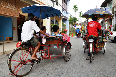 PENANG, MALAYSIA-29 DECEMBER, 2016: Traditional rickshaw driver in Penang, Malaysia. This historical city centre has been listed as a UNESCO World Heritage Site