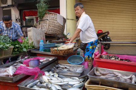 fish vendor: PENANG, MALAYSIA- 29 DECEMBER, 2016: Unidentified seller sell fresh raw fish at local fish market in Penang, Malaysia Editorial