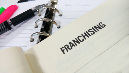 franchising: Franchising word printed on a white book Stock Photo