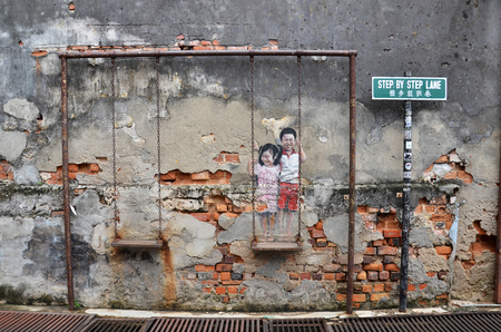 PENANG MALAYSIA-29 DECEMBER 2016: Children on the Swing street art mural by Lithuanian artist Ernest Zacharevic in Penang, Malaysia. Editorial