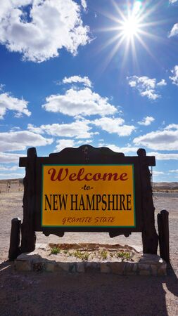 accomplish: Welcome to New Hampshire road sign with blue sky
