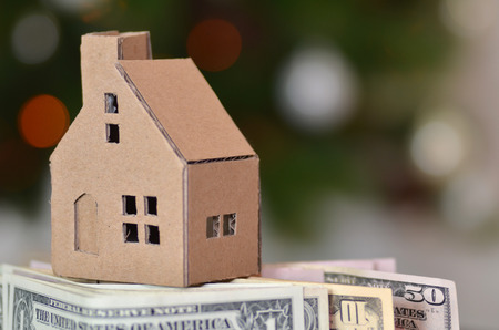 Paper made house stands on dollar money