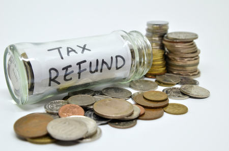 Tax refund lable in a glass jar with coins spilling out isolated on white background Stock Photo
