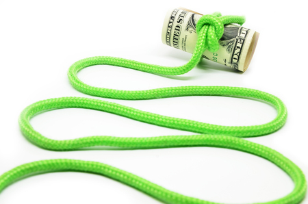 Roll of hundred dollar bills related green rope in knot