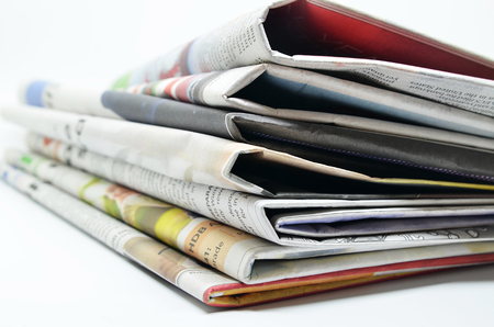 Newspapers folded and stacked isolated on white Stock Photo