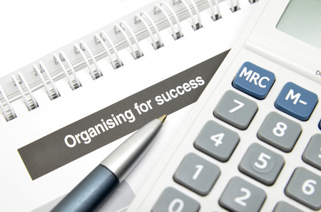 Organising for success printed on book with pen and calculator