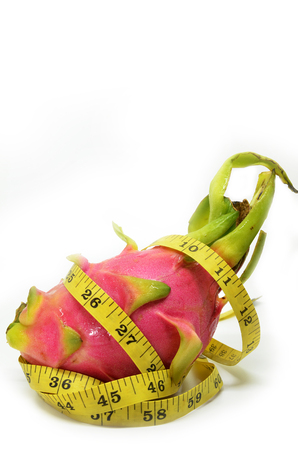 Dragon fruit and measure tape on white background