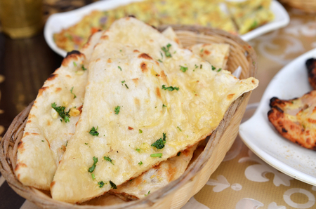 Garlic and coriander naan on a basket. Indian food. Stock Photo