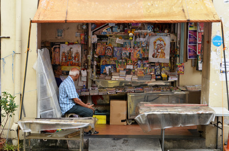 roadside stand: SINGAPORE- APR 09, 2017:  Owner of Indian magazines store along at the roadside of Little India in Singapore Little India is Singaporean neighborhood east of the Singapore River