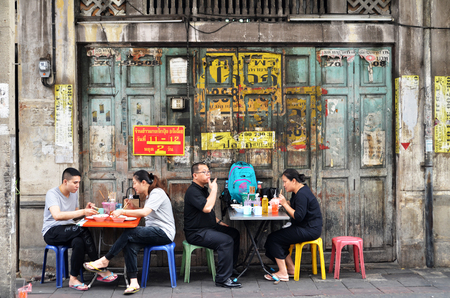 BANGKOK, THAILAND- MAY 19, 2017:  Unidentified man eats on a street in chinatown district, Bangkok, Thailand. Chinatown is renowned for its street food and outdoor dining.