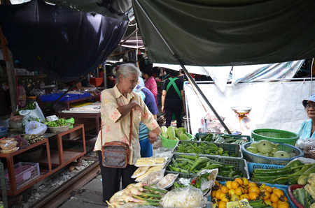 klong: MAE KLONG, THAILAND- MAY 17, 2017: Vendors sell food at Mae Klong railway tracks market in Thailand. The market is notable for its location on active railroad line