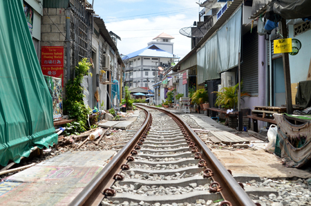 MAE KLONG, THAILAND- MAY 19, 2017: Railroad tracks at Rom Hup Market , Mae Klong Railway Station.Every time the train passes the fresh market all vendors have to move the product away. Editorial