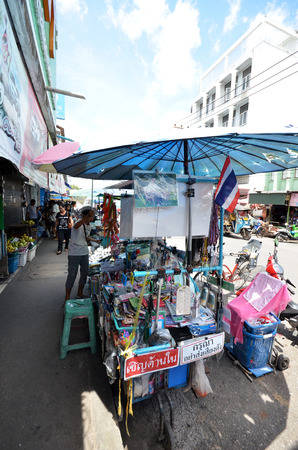 klong: MAE KLONG, THAILAND- MAY 19, 2017: Vendor sells street food on the street in Mae Klong market, Thailand.