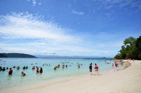 KOTA KINABALU, MALAYSIA- 24 JUN 2017: Tourists enjoy white sand beach of Sapi island in Sabah, Malaysia. Sapi Island is a favorite destination of tourists.