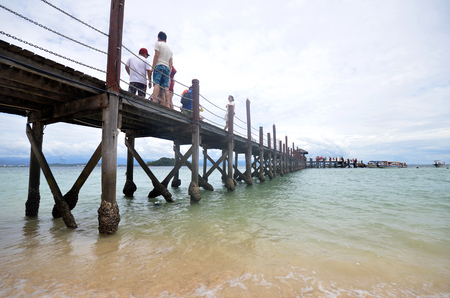 comprise: KOTA KINABALU, MALAYSIA- 24 JUN 2017: Tourists walk on Manukan Island footbridge in Malaysia. The Manukan Island Resort is a hideaway that is one of the five tropical islands that comprise the Tunku Abdul Rahman Park.