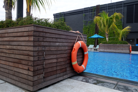 Life ring orange color hanging at wall aside the swimming pool as rescue equipment