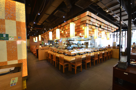 KOTA KINABALU, MALAYSIA- JUN 29, 2017: Interior of a Japanese restaurant bar and lounge in Kota Kinabalu, Malaysia. The main hall with a open kitchen and individual seat along the tables Redactioneel