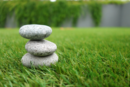 Pebbles stacked up on grass background. Natural concept