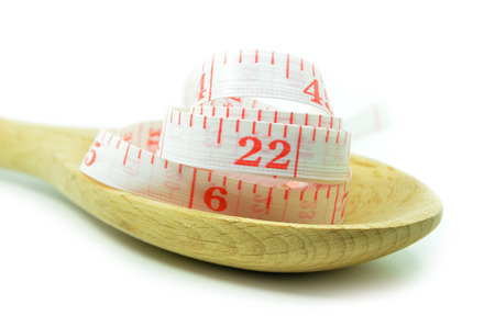 White measurement tape with wooden spoon isolated on white