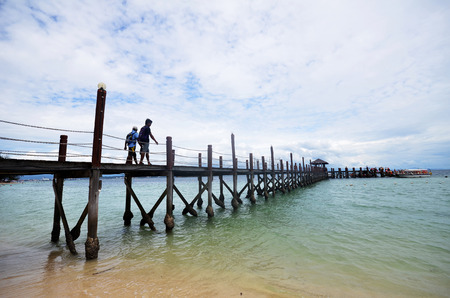 KOTA KINABALU, MALAYSIA- 24 JUN 2017: Tourists walk on Manukan Island footbridge in Malaysia. The Manukan Island Resort is a hideaway that is one of the five tropical islands that comprise the Tunku Abdul Rahman Park.