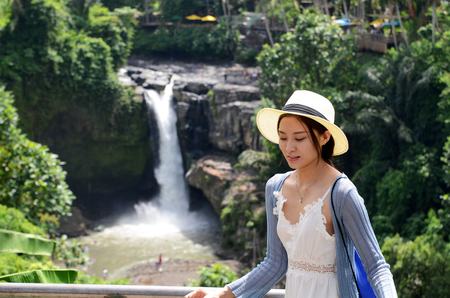 BALI, INDONESIA- 14 FEB, 2019: Young beautiful tourist visiting the Tegenungan waterfall in Bali, Indonesia