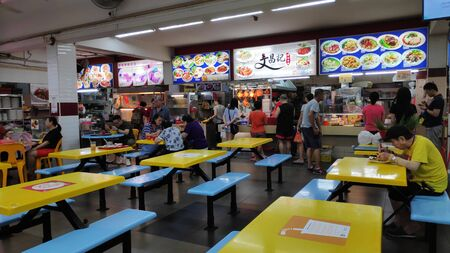 Singapore- 11 Aug, 2019: People at hawker center in Singapore. Hawker centre or cooked food centre is an open-air complex in Singapore Editorial