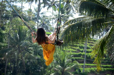 Young woman swinging in the jungle rainforest of Bali island, Indonesia