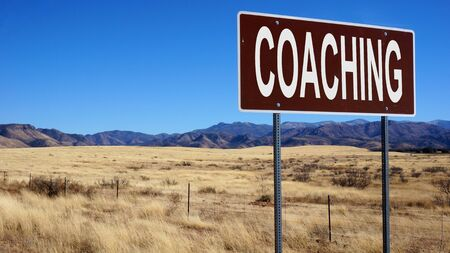 Coaching word on road sign and blue sky