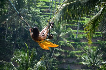 Young woman swinging in the jungle rainforest of Bali island, Indonesia Stock Photo