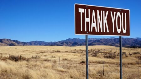 Thank you word on road sign and blue sky.