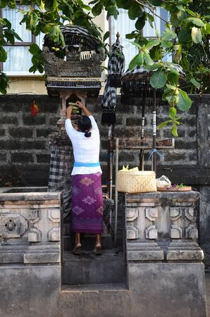 Bali, Indonesia- 18 Oct, 2019: A woman praying at a Temple off the street in Bali Indonesia. Sajtókép