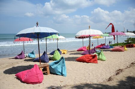 Bali, Indonesia- 18 Oct, 2019: Empty beach background with bright tent, chairs, surf waves and sunny sky