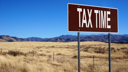 Tax time word on road sign and blue sky.