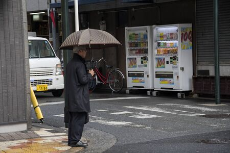 Osaka, Japan- 02 Dec, 2019: Businessman with umbrella wait to cross street during rainy day