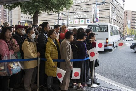 Kyoto, Japan- 27 Nov, 2019: Crowds with paper flags waiting for the Japanese Emperor Akihito and his family in Kyoto.