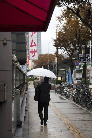 Osaka, Japan- 02 Dec, 2019: Businessman with umbrella on street during rainy day
