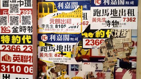 Hong Kong- 13 Jan, 2020: Commercial property advertised for sale or rent on posters at a building wall in the bustling city of Hong Kong