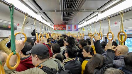 Kyoto, Japan-26 nov 2019: Passagiers rijden in een drukke metrotrein in Kyoto.