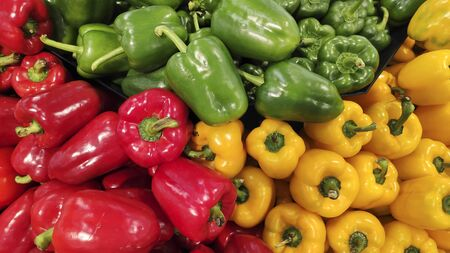 Green, yellow and orange attractive peppers on the market