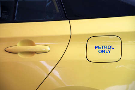 Petrol only printed on the opening of refuel tank on yellow car Reklamní fotografie