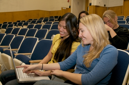 Multicultural Students studying with laptop in lecture hall